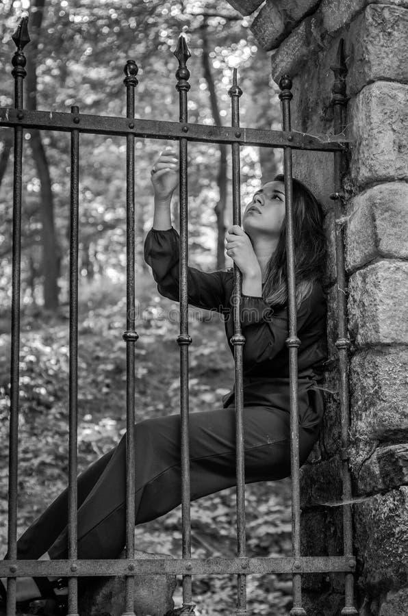 A mulher encantador nova com o delinquente longo do cabelo, senta-se atrás das barras em um prisioneiro de pedra antigo da prisão fotos de stock