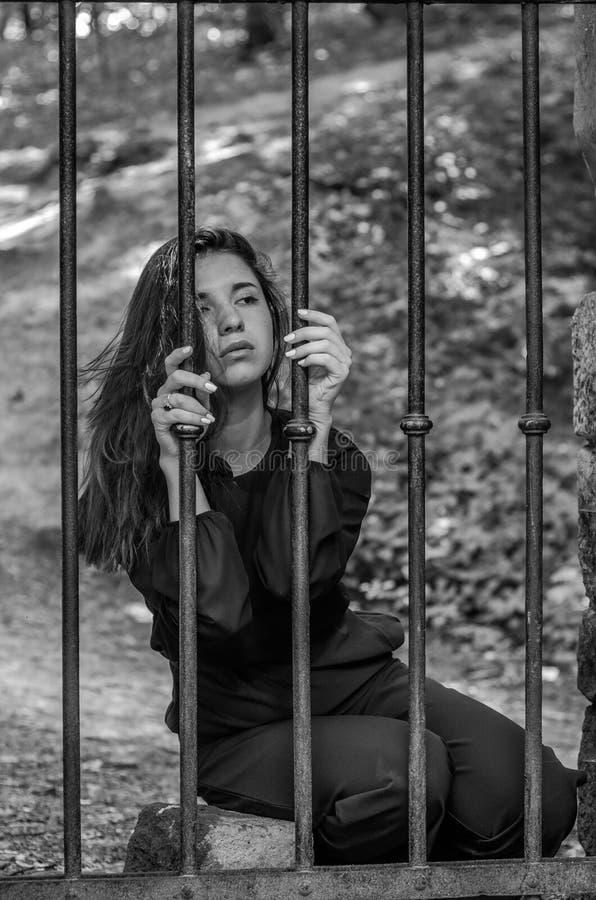 A mulher encantador nova com o delinquente longo do cabelo, senta-se atrás das barras no prisioneiro de pedra idoso da cadeia e o imagem de stock royalty free