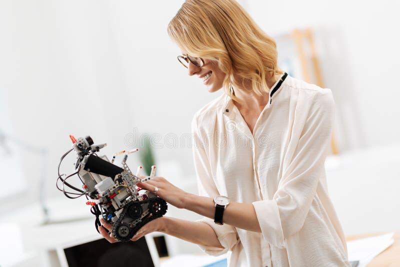 Mulher encantador que explora pouco robô no escritório foto de stock