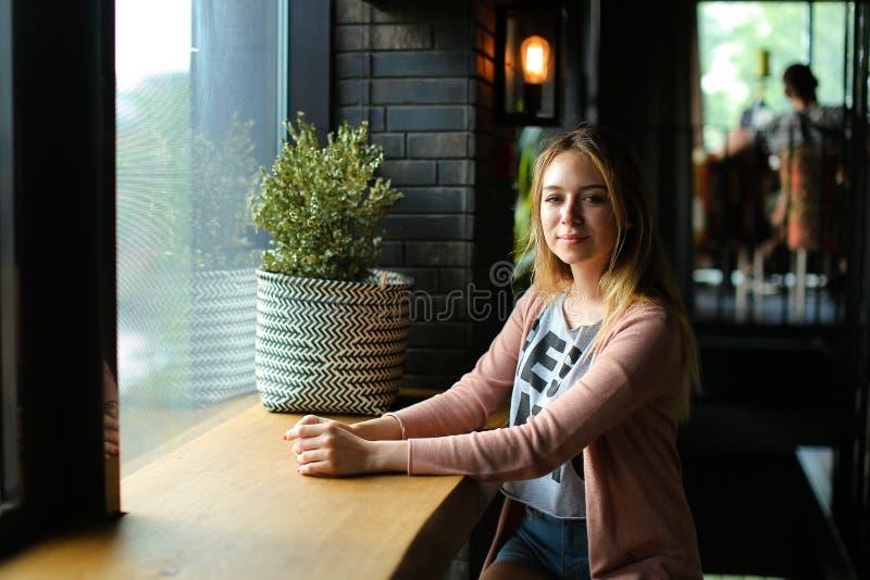 Mulher encantador que senta-se perto da janela no café e no sonho imagens de stock royalty free