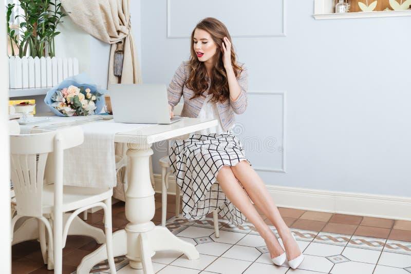 Mulher encantador que usa o portátil na tabela no café fotografia de stock royalty free