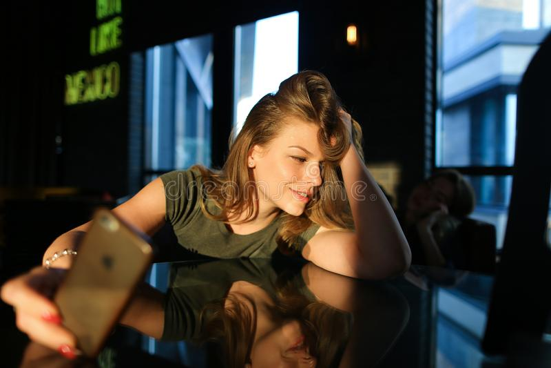 A mulher encantador que usa o smartphone no café no sol irradia imagens de stock royalty free