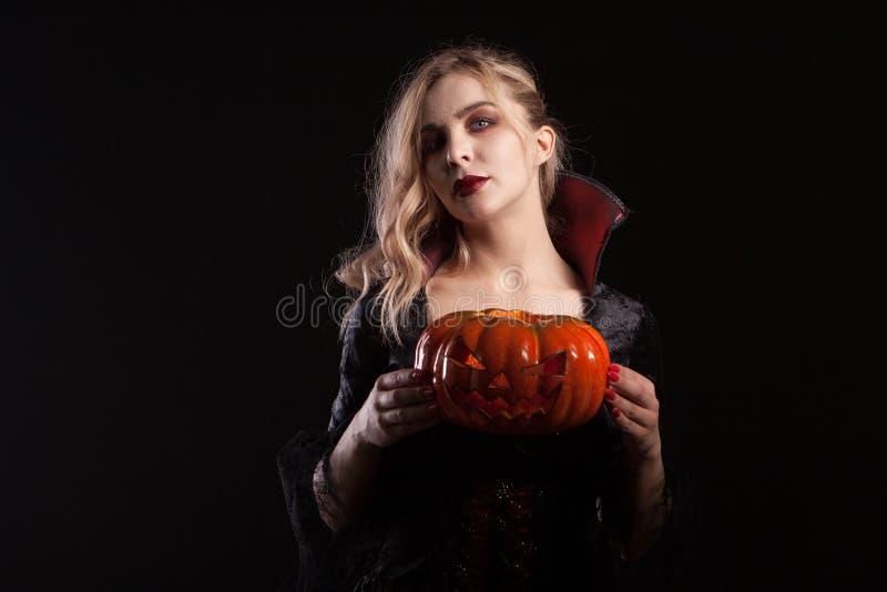 Mulher encantadora com fantasia de vampiro segurando abóbora de halloween em fundo escuro foto de stock royalty free