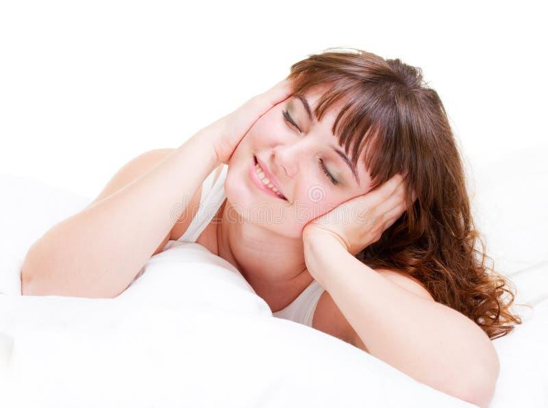 A mulher encantadora está encontrando-se na cama fotografia de stock