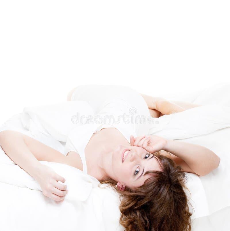 Mulher encantadora que descansa na cama branca foto de stock