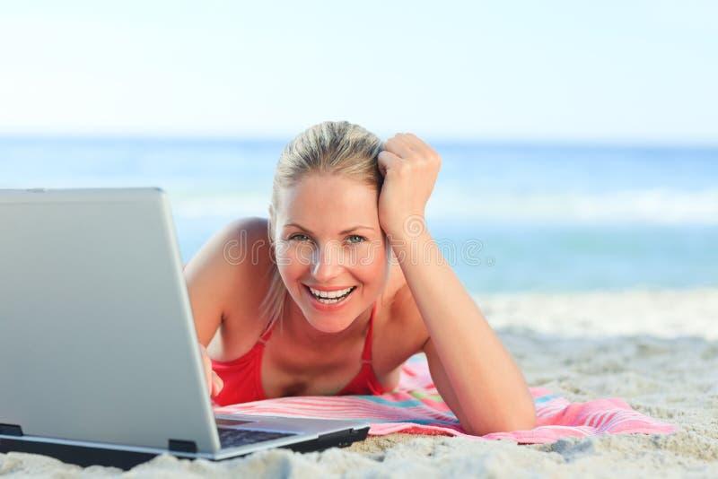 Mulher encantadora que trabalha em seu portátil na praia imagens de stock royalty free
