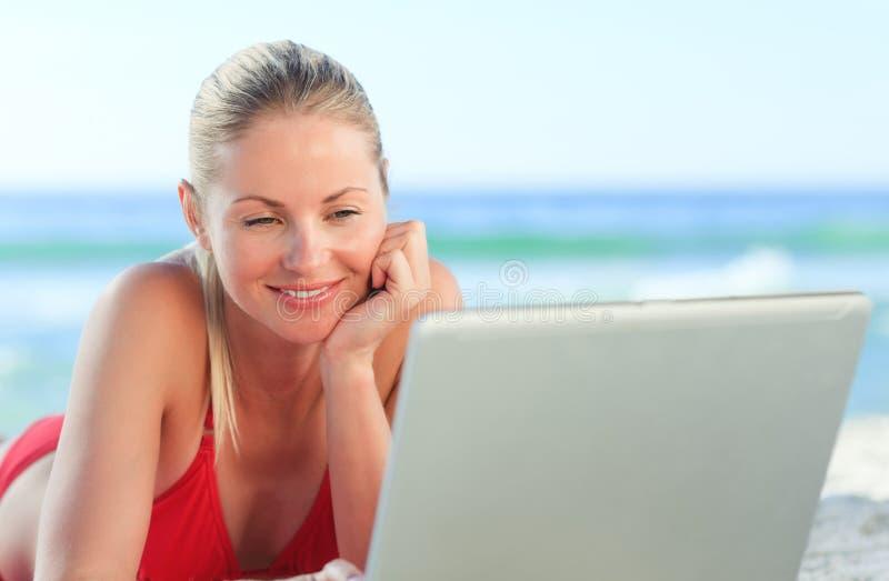 Mulher encantadora que trabalha em seu portátil na praia imagem de stock royalty free