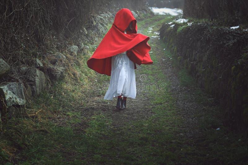 Mulher encapuçado vermelha em uma estrada secundária escura imagens de stock