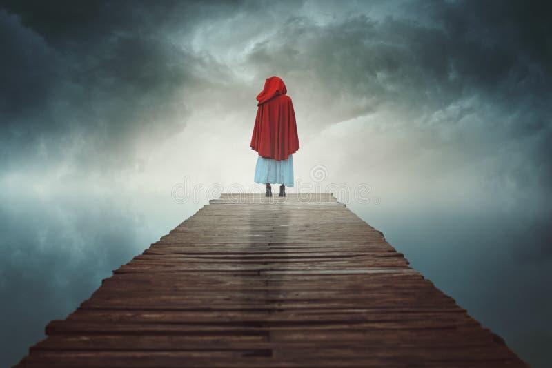 A mulher encapuçado vermelha perdeu em uma terra surreal fotos de stock
