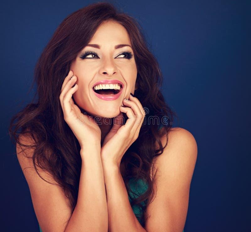 Mulher encaracolado bonita de riso do penteado que olha com mout aberto foto de stock