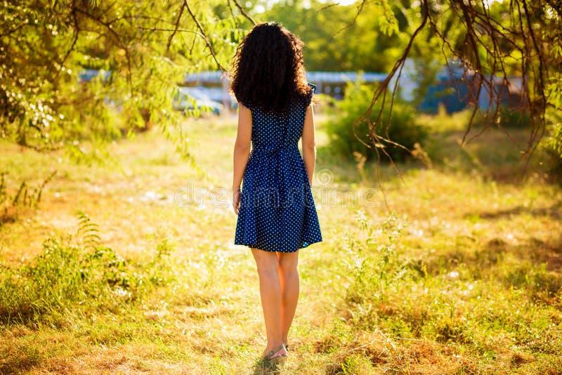 Mulher encaracolado bonita que levanta no vestido no por do sol imagens de stock royalty free