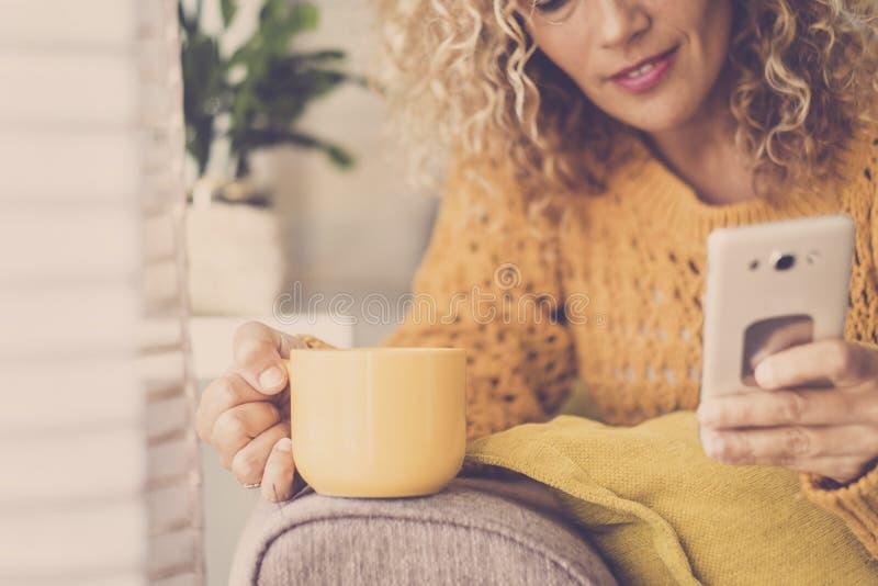 Mulher encaracolado loura agradável da Idade Média em casa que bebe o chá ou o café e que usa o celular com busca da Web da tecno foto de stock