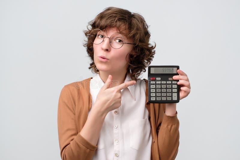 Mulher encaracolado nova bonita com a calculadora, dando o advie imagem de stock