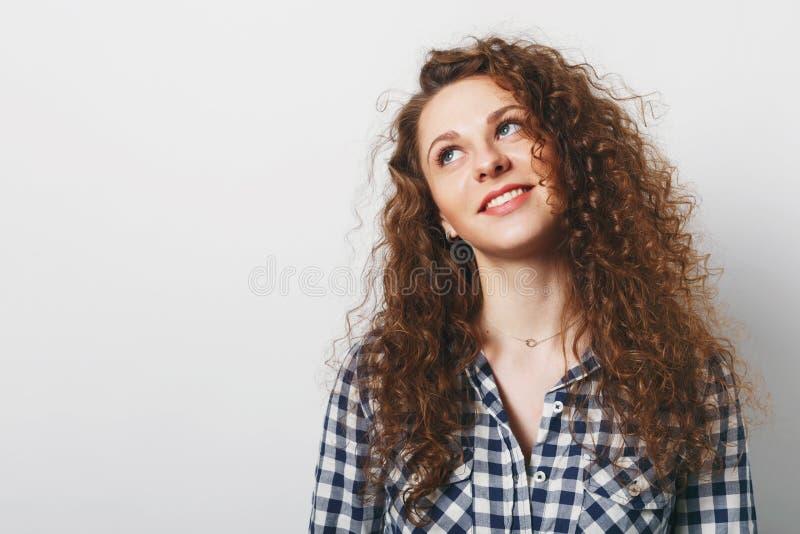 A mulher encaracolado sonhadora com o olhar atrativo, vestido na camisa quadriculado, levanta contra o fundo branco, pensa sobre  fotografia de stock