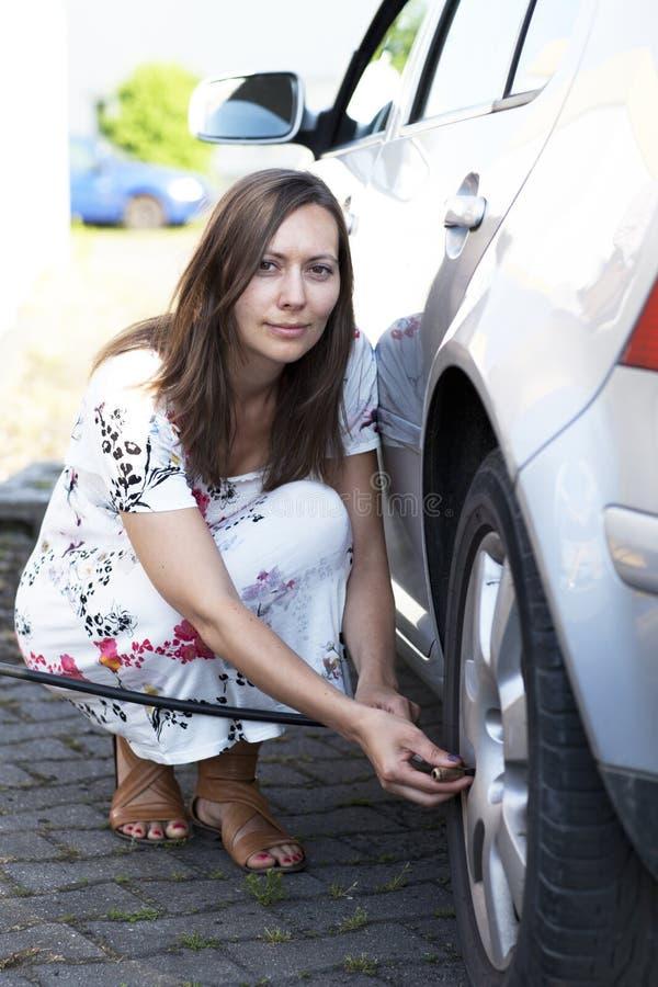 A mulher enche o pneu fotografia de stock