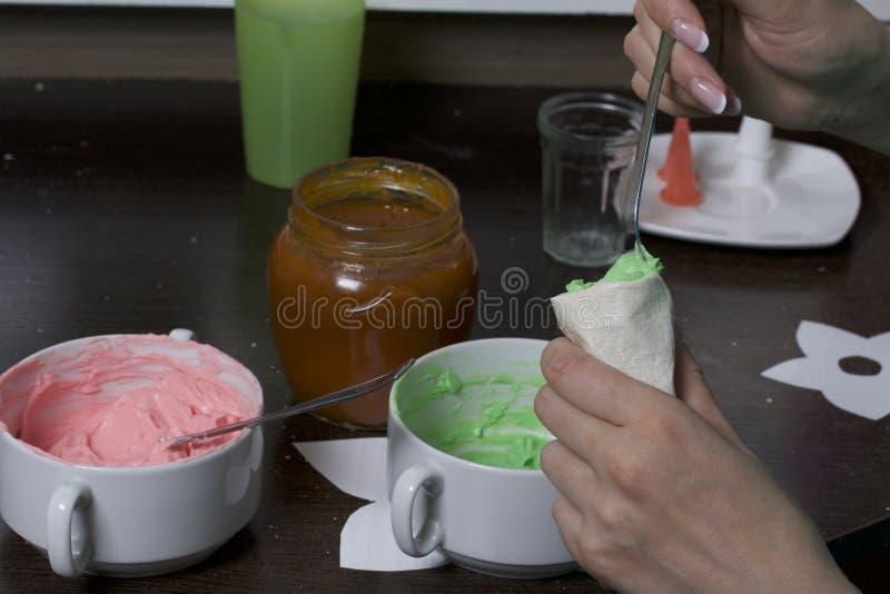 A mulher enche um saco da pastelaria com o creme Creme de cores diferentes para decorar a cesta do bolo Está próximo um frasco  foto de stock royalty free