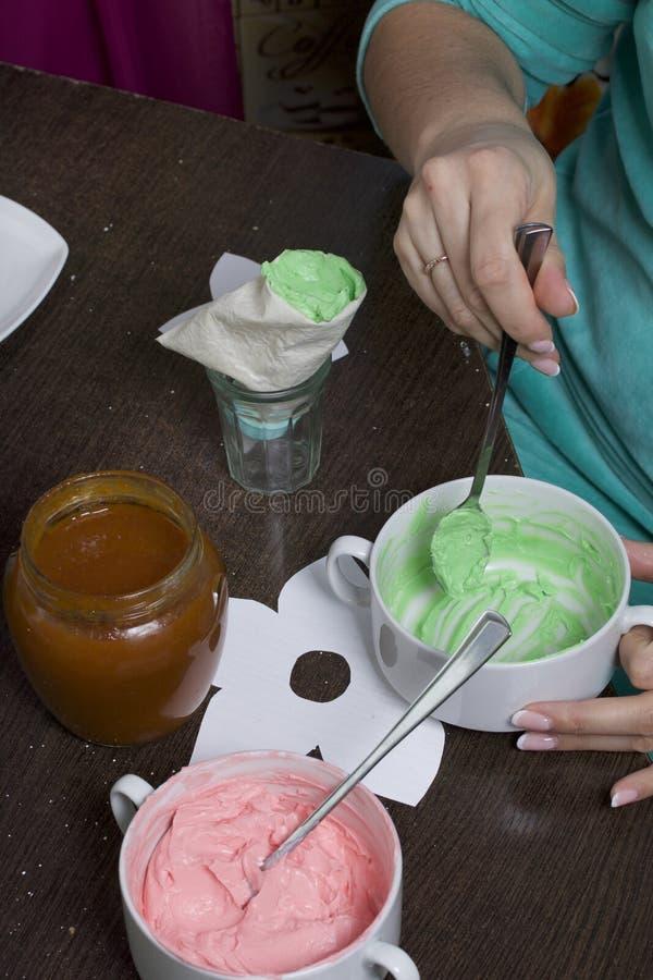 A mulher enche um saco da pastelaria com o creme Creme de cores diferentes para decorar a cesta do bolo Está próximo um frasco  imagem de stock