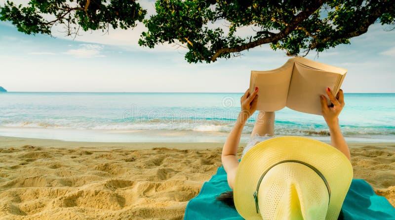 A mulher encontra-se para baixo na toalha verde que põe sobre a praia da areia sob a árvore e a leitura de um livro Vida lenta em fotos de stock royalty free