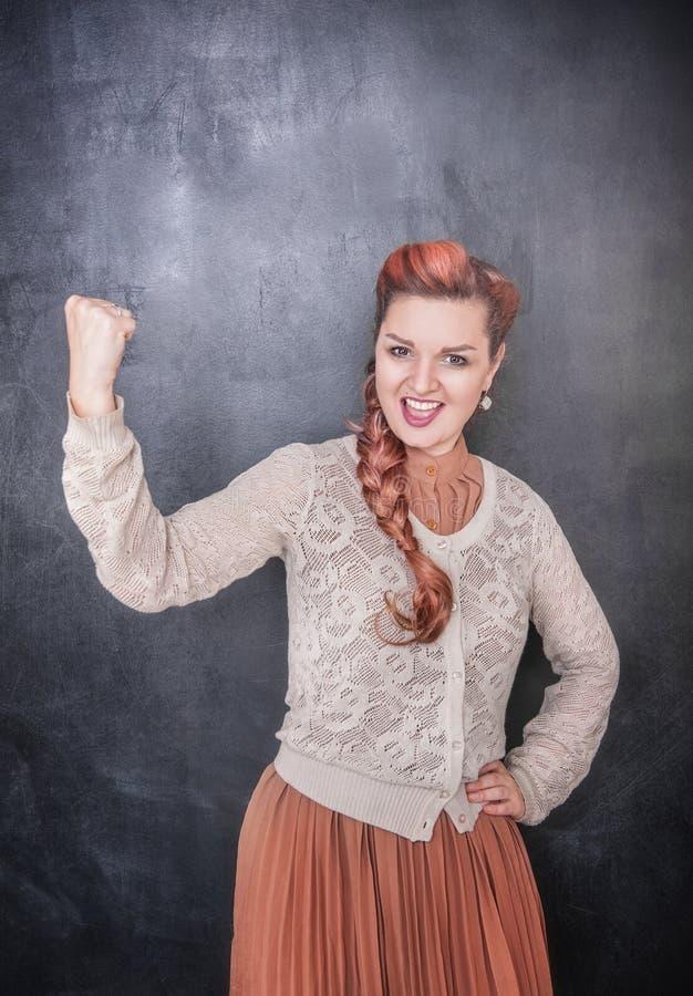 Mulher engraçada com gesto do yes no fundo do quadro-negro imagem de stock royalty free
