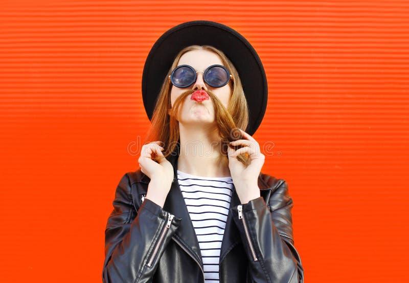A mulher engraçada da forma que tem o divertimento mostra o cabelo do bigode sobre o vermelho colorido imagens de stock royalty free