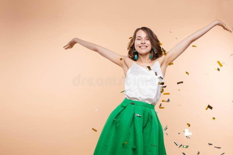 Mulher engraçada feliz que aumenta a mão cercada por confetes coloridos de brilho de queda foto de stock