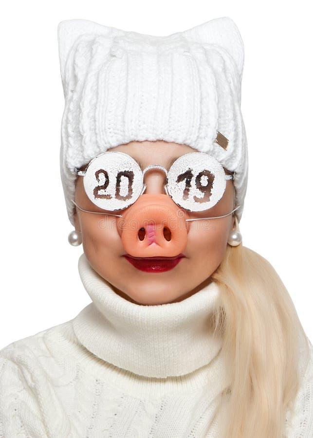 Mulher engraçada nos vidros com o nariz da inscrição 2019 e de um porco foto de stock royalty free