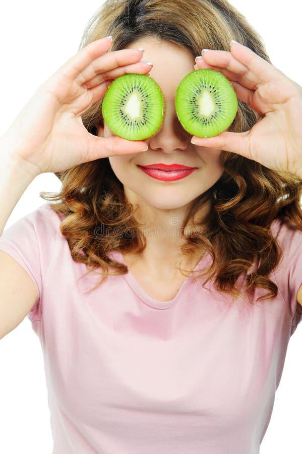 Jovem mulher que guardara o fruto de quivi para seus olhos imagens de stock