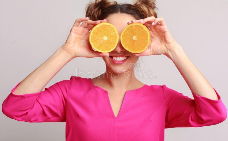 Mulher engraçada que mantém metades das laranjas contra o fundo fotos de stock