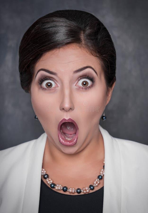 Mulher engraçada surpreendida no fundo do quadro-negro fotografia de stock