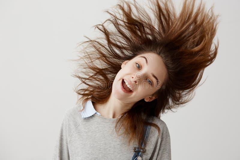 A mulher engraçada vestiu-se na camiseta que engana ao redor a agitação de sua cabeça com cabelo de flutuação Melômano fêmea feli imagem de stock royalty free