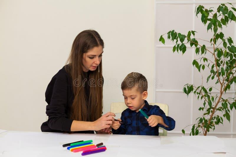 A mulher ensina a um menino novo marcadores da pintura fotografia de stock royalty free