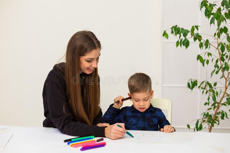 A mulher ensina a um menino novo marcadores da pintura fotografia de stock