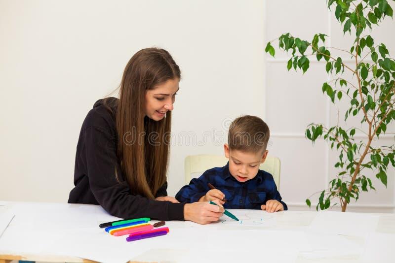 A mulher ensina a um menino novo marcadores da pintura foto de stock royalty free