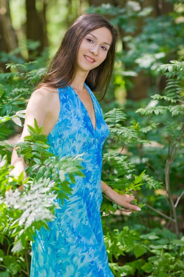 Mulher entre as folhas do verde na floresta fotos de stock