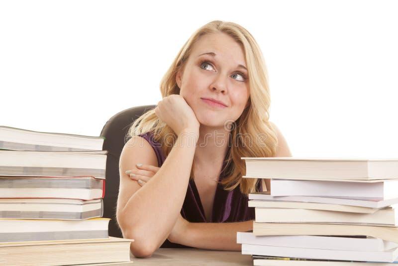 A mulher entre pilhas de livro pensa foto de stock royalty free