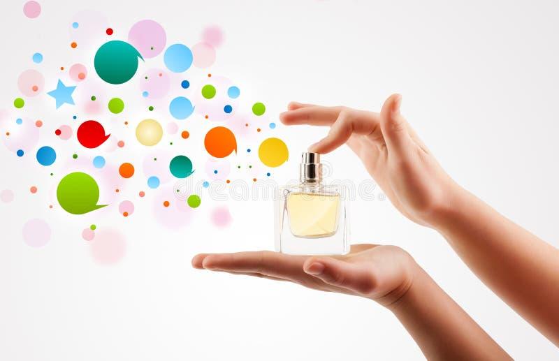 a mulher entrega bolhas coloridas de pulverização da garrafa de perfume bonita foto de stock