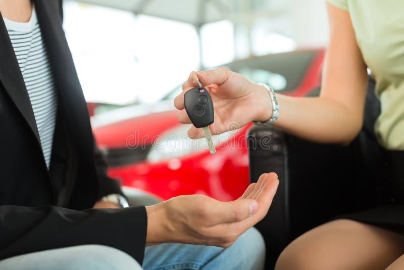 A mulher entrega chaves do carro a um homem no auto negociante fotos de stock royalty free