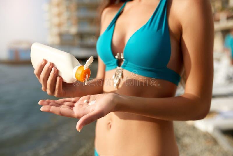 A mulher entrega a colocação da proteção solar de uma garrafa do creme do bronzeado Suncream fêmea caucasiano do aperto em sua mã imagem de stock