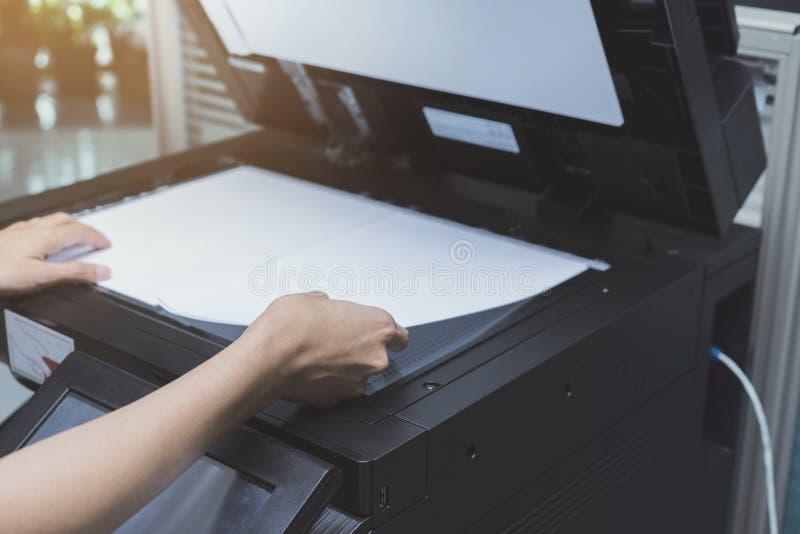 A mulher entrega a colocação de uma folha de papel em um dispositivo de copi fotos de stock