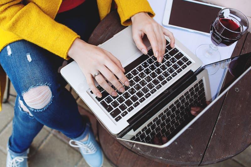 A mulher entrega a datilografia na tabuleta e no vinho do portátil no café imagens de stock