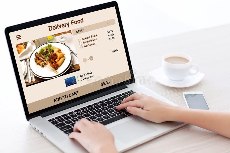 A mulher entrega a datilografia no teclado do portátil com a tela do alimento da entrega imagem de stock royalty free