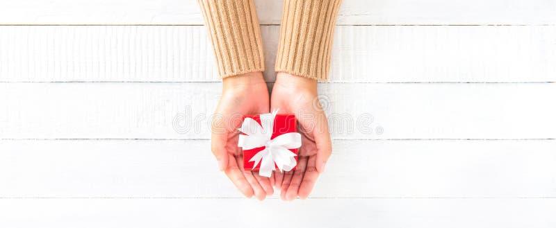 A mulher entrega a doação da caixa de presente vermelha pequena no fundo de madeira branco fotos de stock