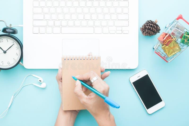 A mulher entrega a escrita no caderno, o espaço de funcionamento com portátil, a compra em linha e o mercado imagem de stock royalty free