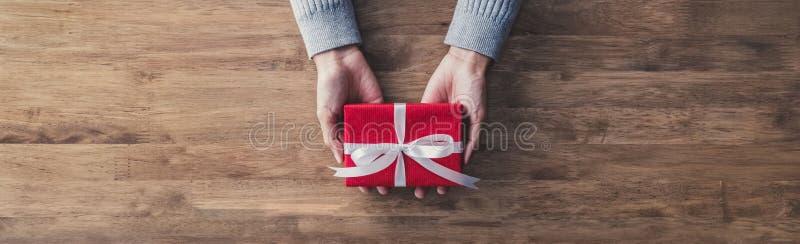 A mulher entrega guardar a caixa de presente vermelha em uma tabela imagem de stock