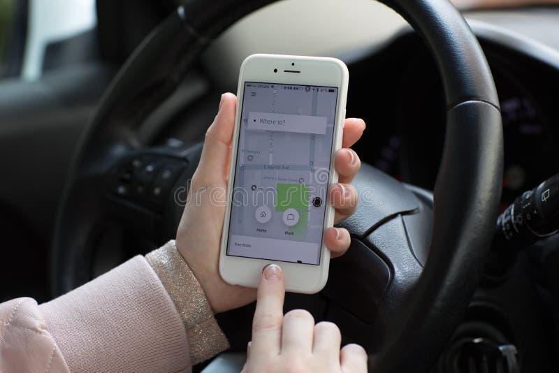 A mulher entrega guardar o iPhone 6S com táxi Uber da aplicação foto de stock royalty free