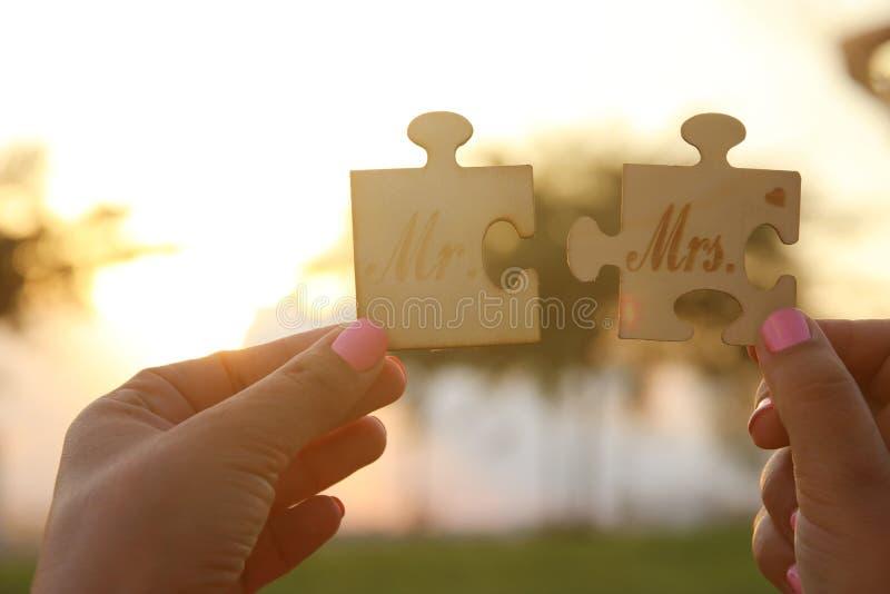 A mulher entrega guardar o Sr. e a Sra. sinal durante o tempo do por do sol conceito da harmonia e do casamento imagem de stock