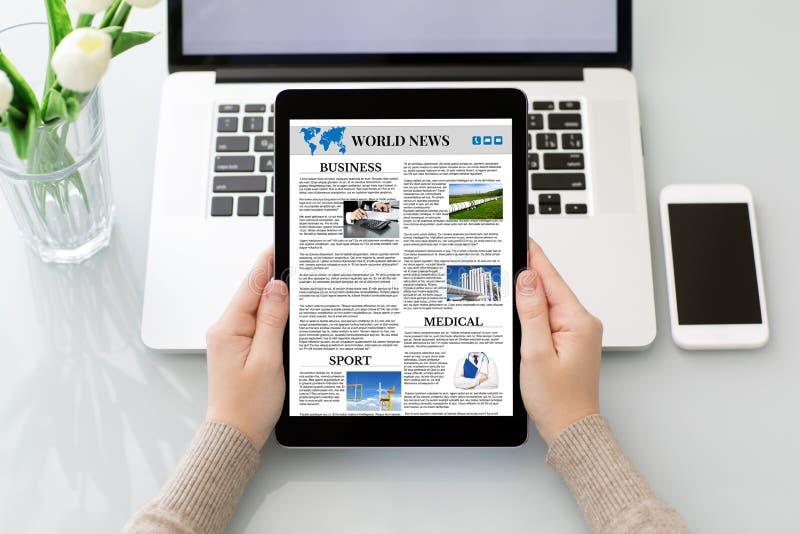 A mulher entrega guardar o tablet pc com a tela das notícias do mundo do app fotografia de stock royalty free