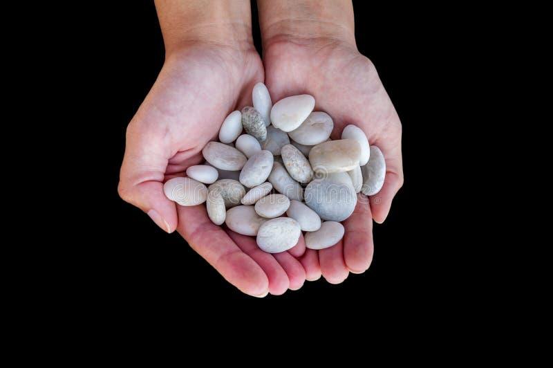 A mulher entrega guardar pedras pequenas nas mãos isoladas no preto fotografia de stock
