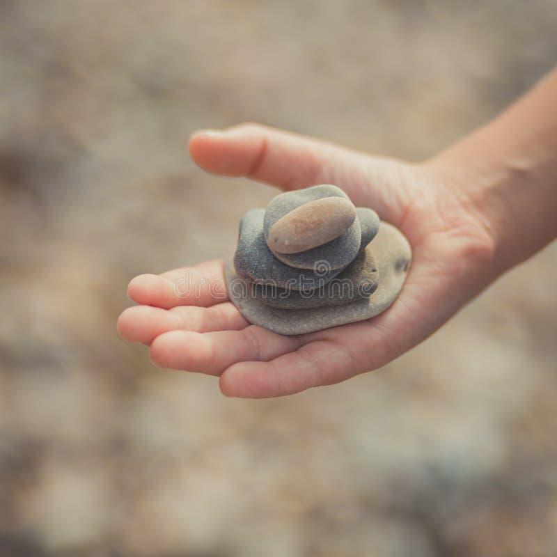 A mulher entrega guardar pedras pequenas nas mãos no fundo da praia com sol ardente imagens de stock royalty free