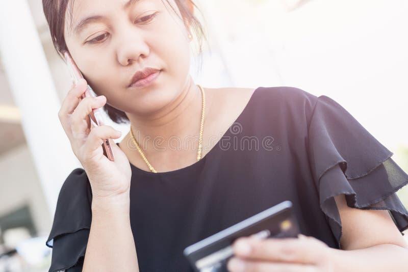 A mulher entrega guardar/que usa o smartphone e o cartão de crédito na frente de imagens de stock royalty free